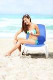 Vrouw die op strand zonneschermlotion toepast royalty-vrije stock afbeelding