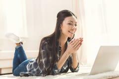 Vrouw die op tapijt liggen en handen slaan stock afbeeldingen