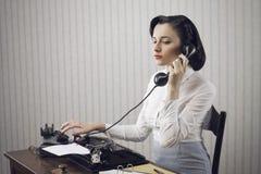 Vrouw die op telefoon bij bureau spreken royalty-vrije stock afbeeldingen