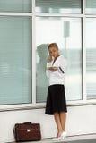 Vrouw die op telefoon dichtbij bureau spreekt Stock Fotografie