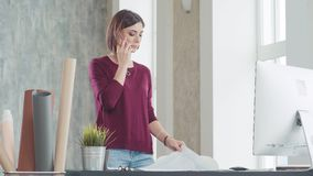 Vrouw die op telefoon spreken, die zich voor lijst in een helder bureau bevinden stock footage