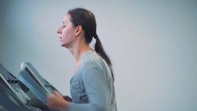 Vrouw die op tredmolen in gymnastiek loopt stock video