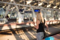 Vrouw die op trein op stationplatform wachten stock afbeeldingen
