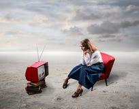 Vrouw die op TV let stock fotografie