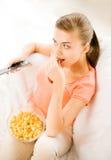 Vrouw die op TV letten en popcorn eten Stock Afbeeldingen