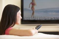 Vrouw die op TV Met groot scherm thuis letten Stock Fotografie
