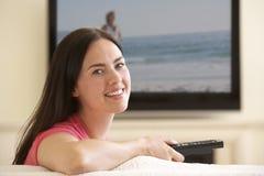 Vrouw die op TV Met groot scherm thuis letten Stock Foto