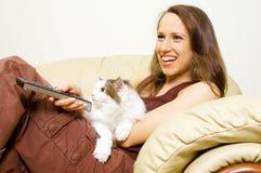 Vrouw die op TV met haar kat let Royalty-vrije Stock Afbeeldingen