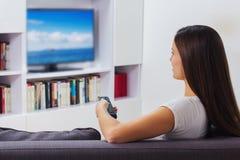Vrouw die op TV thuis let Royalty-vrije Stock Foto's