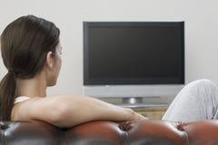 Vrouw die op TV in Woonkamer letten Stock Fotografie
