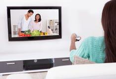 Vrouw die op TV in Woonkamer letten Stock Foto
