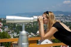 Vrouw die op vakantie door verrekijkers kijkt Stock Afbeeldingen