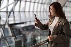 vrouw die op vlucht wachten en smartphone in luchthaven met behulp van royalty-vrije stock afbeeldingen