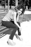 Vrouw die op vriendzitting wachten op bank in park Stock Fotografie