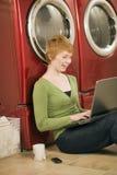 Vrouw die op wasserij wacht Stock Fotografie