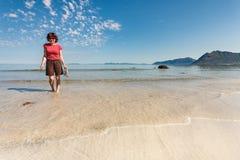 Vrouw die op zandig strand, Lofoten Noorwegen lopen stock afbeeldingen