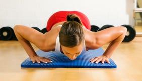 Vrouw die opdrukoefeningen in gymnastiek doet Royalty-vrije Stock Foto