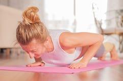 Vrouw die opdrukoefeningen op yogamat thuis doen Geschiktheidsmeisje die opdrukoefeningen op oefeningsmat doen stock afbeelding