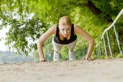 Vrouw die opdrukoefeningen in openlucht doet Royalty-vrije Stock Foto's