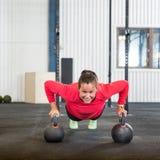 Vrouw die Opdrukoefeningoefening met Kettlebell doen Royalty-vrije Stock Afbeeldingen