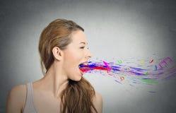 Vrouw die open mond kleurrijke plonsnota's zingen die wegvliegen stock fotografie