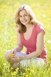 Vrouw die in openlucht bloem het glimlachen houdt Royalty-vrije Stock Foto's