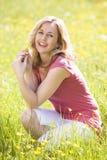 Vrouw die in openlucht bloem het glimlachen houdt Stock Afbeeldingen