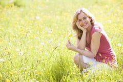 Vrouw die in openlucht bloem het glimlachen houdt Stock Foto's