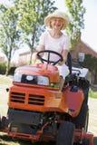 Vrouw die in openlucht grasmaaier het glimlachen drijft Stock Afbeelding
