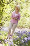 Vrouw die in openlucht het houden van bloem het glimlachen loopt Royalty-vrije Stock Afbeeldingen