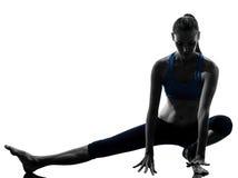 Vrouw die opwarming van yoga de uitrekkende benen uitoefenen Stock Afbeeldingen