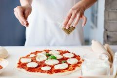 Vrouw die orego op ruwe pizza toevoegen royalty-vrije stock afbeelding