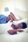 Vrouw die oren behandelen met hoofdkussen terwijl haar echtgenoot snurkt Stock Foto's