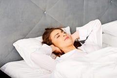 Vrouw die oren behandelen met hoofdkussen wegens lawaai royalty-vrije stock afbeelding