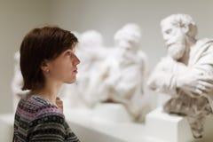 Vrouw die oude beeldhouwwerken kijken Royalty-vrije Stock Fotografie
