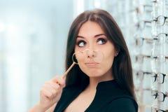 Vrouw die Oude Face-à-mainglazen met Nieuw Paar kijken te vervangen Stock Foto's