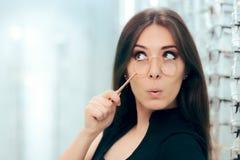 Vrouw die Oude Face-à-mainglazen met Nieuw Paar kijken te vervangen Stock Afbeelding