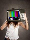 Vrouw die oude televisie op haar hoofd houden stock afbeelding