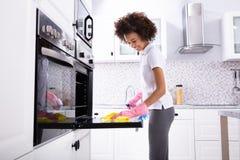 Vrouw die Oven With Napkin schoonmaken stock foto