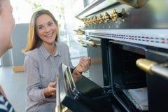 Vrouw die oven tonen aan klant royalty-vrije stock foto's