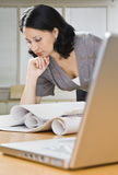 Vrouw die over Blauwdrukken kijkt Stock Foto's