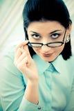 Vrouw die over glazen kijkt Stock Fotografie