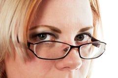 Vrouw die over haar glazen kijkt Stock Foto's