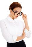 Vrouw die over haar glazen turen Royalty-vrije Stock Afbeelding