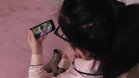 Vrouw die over het krijgen van videobericht op smartphone informeren stock footage