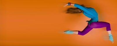 Vrouw die over oranje achtergrond springt Stock Afbeeldingen