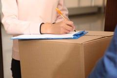 Vrouw die pakket van de koerier van de leveringsdienst binnen ontvangen royalty-vrije stock fotografie