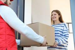 Vrouw die pakket van de koerier van de leveringsdienst ontvangen stock fotografie