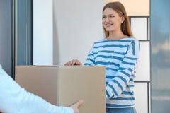 Vrouw die pakket van de koerier van de leveringsdienst ontvangen royalty-vrije stock afbeelding