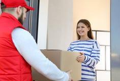 Vrouw die pakket van de koerier van de leveringsdienst ontvangen stock foto